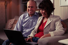 A smiling pair sitting on the sofa indoors watching in laptop Stock Photography