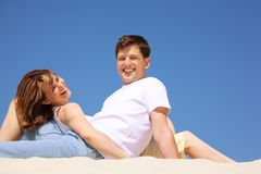 Smiling pair in white shirts on the beach Royalty Free Stock Images