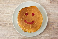 Smiling pancake. On a plate Royalty Free Stock Image