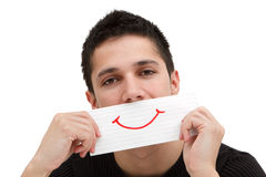 A smiling paper in the hand of a young man. A handsome young man holding a ruled paper with a red smile on it Royalty Free Stock Images