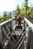 Tourist on The trail trees Lipno Lookout. Smiling Papuan tourist girl - young woman in purple jacket and black pants passing obstacles high on The trail trees Royalty Free Stock Photos