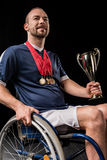 Smiling paralympic in wheelchair with gold medals on neck holding champion goblet Stock Photography