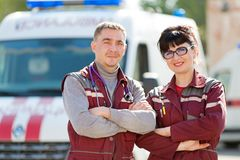 Smiling paramedics on ambulance car background Royalty Free Stock Photo