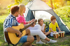 Smiling parent and children enjoying on camping Royalty Free Stock Image