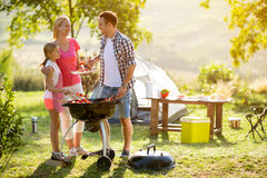 Smiling parent grilling meat with daughter. On camping Royalty Free Stock Photography