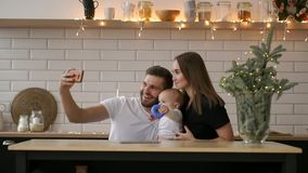 Smiling parents with baby taking selfie family photo on bed at home.  stock video footage