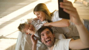 Smiling parents with baby taking selfie family photo on bed at home stock video footage