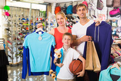 Smiling parents with boy in sport store. Smiling parents with boy in school age shopping clothing in sport store Stock Photos