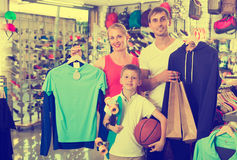 Smiling parents with boy in sport store. Smiling parents with boy in school age shopping clothing in sport store Royalty Free Stock Photos