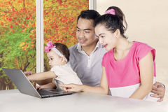 Smiling parents and child looking at laptop Stock Photo