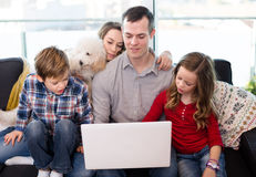 Smiling parents with children enjoying movie on laptop together Stock Photo