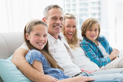 Smiling parents and children sitting together on couch Royalty Free Stock Images