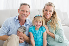 Smiling parents and daughter sitting with rabbit together Royalty Free Stock Image