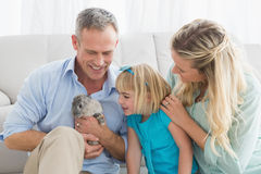 Smiling parents and daughter sitting with rabbit together Royalty Free Stock Images
