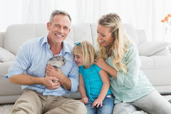 Smiling parents and daughter sitting with rabbit together Stock Images