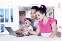 Smiling parents and girl looking at laptop Stock Photography