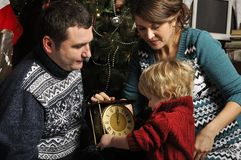 Smiling parents giving Christmas clock to son at home. Smiling parents giving Christmas present to son stock images