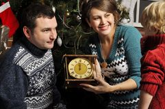 Smiling parents giving Christmas clock to son at home Royalty Free Stock Photo