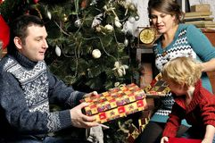 Smiling parents giving Christmas present to son at home Stock Photography