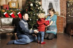 Smiling parents giving Christmas present to son at home. Smiling parents giving Christmas present to son Stock Images