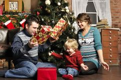 Smiling parents giving Christmas present to son at home Royalty Free Stock Image