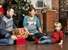 Smiling parents giving Christmas present to son at home. Smiling parents giving Christmas present to son Stock Photos