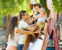 Smiling parents helping kids on slide Stock Image