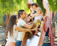 Smiling parents helping kids on slide Stock Image