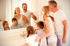 Parents and kids brushing teeth in bathroom. Smiling parents and kids brushing teeth in bathroom at home royalty free stock photos