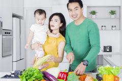 Smiling parents and little girl cook vegetables. Portrait of smiling parents and little girl cooking vegetables together while looking at the camera Royalty Free Stock Photos