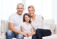 Smiling parents and little girl at home. Family, child and home concept - smiling parents and little girl at home royalty free stock photo