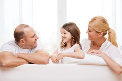 Smiling parents and little girl at home. Family, child and home concept - smiling parents and little girl at home Stock Photography