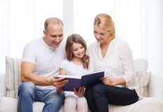 Smiling parents and little girl with at home. Family, child and home concept - smiling parents and little girl with book at home stock photography