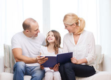 Smiling parents and little girl with at home. Family, child and home concept - smiling parents and little girl with book at home royalty free stock image