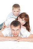 Smiling parents with little son lying on white bed Royalty Free Stock Photography