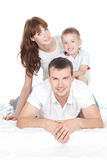 Smiling parents with little son lying on white bed Royalty Free Stock Photos
