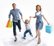 Parents with shopping bags holding hands together with excited son isolated on white Royalty Free Stock Image