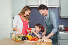 Smiling parents with son in kitchen. Son holding bell pepper with parents in kitchen at home Royalty Free Stock Photo
