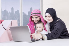 Smiling parents and son looking at laptop Stock Photo