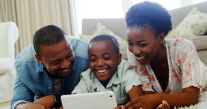 Parents and son lying on rug and using digital tablet in living room. Smiling parents and son lying on rug and using digital tablet in living room at home stock video