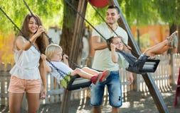 Smiling parents swinging children Royalty Free Stock Photo
