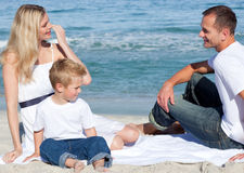 Smiling parents with their son sitting on the sand. At the beach Royalty Free Stock Image
