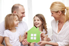 Smiling parents and two little girls at new home. Family, children, accommodation and home concept - smiling parents and two little girls at home with green royalty free stock images
