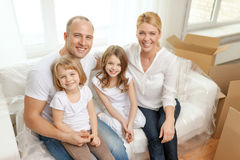 Smiling parents and two little girls at new home Royalty Free Stock Photos
