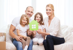 Smiling parents and two little girls at new home Stock Photos
