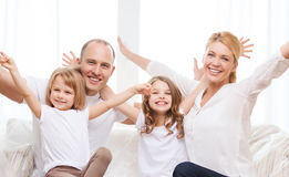 Smiling parents and two little girls at new home Royalty Free Stock Image