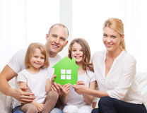Smiling parents and two little girls at new home. Real estate, family, children and home concept - smiling parents and two little girls holding green house stock image