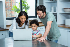 Smiling parents using laptop with son Royalty Free Stock Image