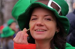 Smiling participant in green hat at the St. Patrick`s Day Parade in the park Sokolniki in Moscow royalty free stock image