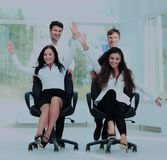 Smiling partners playing together with swivel chair in the offic Stock Images